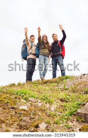 travel, tourism, hike, gesture and people concept - group of smiling friends with backpacks waving hands outdoors - stock photo