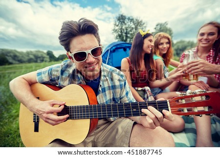 travel, tourism, hike, leisure and people concept - happy man with friends playing guitar at camping - stock photo
