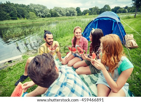 travel, tourism, hike, picnic and people concept - group of happy friends with tent eating watermelon at camping - stock photo