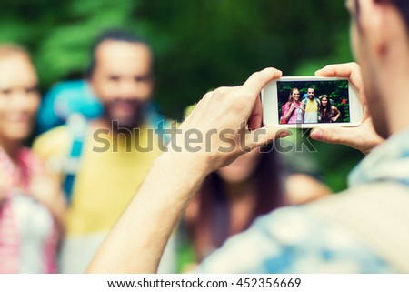 travel, tourism, hike, technology and people concept - close up of man photographing friends with backpacks by smartphone outdoors