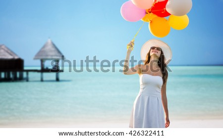 travel, tourism, summer, holidays and people concept - smiling young woman wearing sunglasses with balloons over exotic tropical beach and bungalow background - stock photo