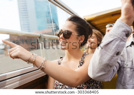 travel, tourism, summer vacation, sightseeing and people concept - happy teenage girl in sunglasses with group of friends traveling by tour bus - stock photo