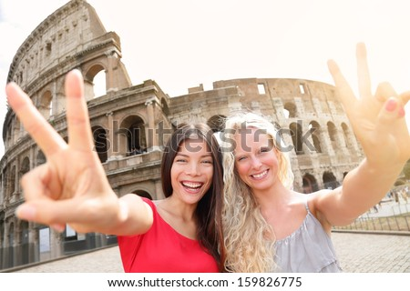 Travel tourist girl friends by Colosseum, Rome. Happy girlfriends tourists showing victory hand sign gesture in front of Coliseum. Beautiful young happy blonde girl and multiracial Asian woman, Italy. - stock photo
