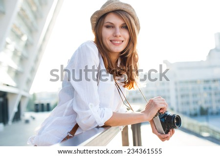Travel tourist woman with camera / photography of young Caucasian woman outdoors  - stock photo