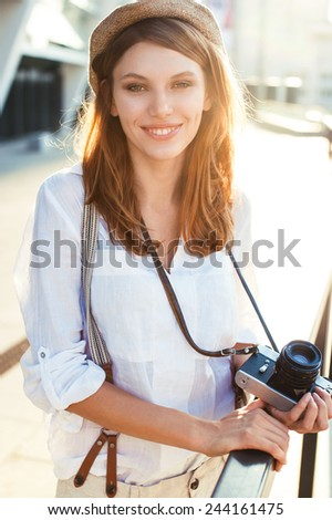 Travel tourist woman with camera. Tourism concept / photography of young Caucasian woman outdoors  - stock photo