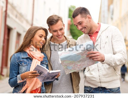 travel, vacation and friendship concept - group of smiling friends with city guide and map exploring city - stock photo