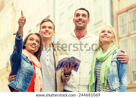 travel, vacation and friendship concept - group of smiling friends with city guide exploring town - stock photo