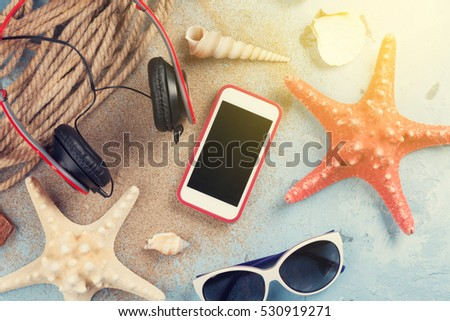 Travel vacation items on stone background. Smartphone, headphones and sunglasses. Top view. Sunny toned