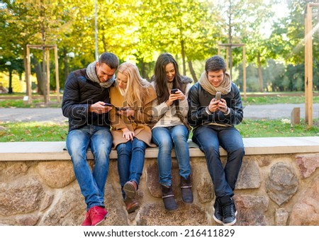 travel, vacation, people, technology and friendship concept - group of smiling friends with smartphones in city park - stock photo