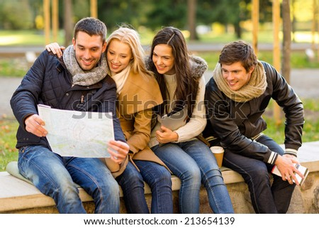 travel, vacation, people, tourism and friendship concept - group of smiling friends sitting with tablet pc computer city guide and map in park