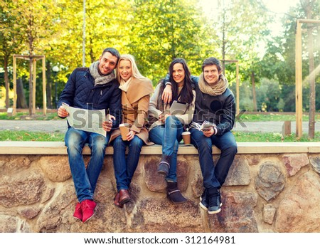 travel, vacation, people, tourism and friendship concept - group of smiling friends sitting with tablet pc computer map and hot drinks in park