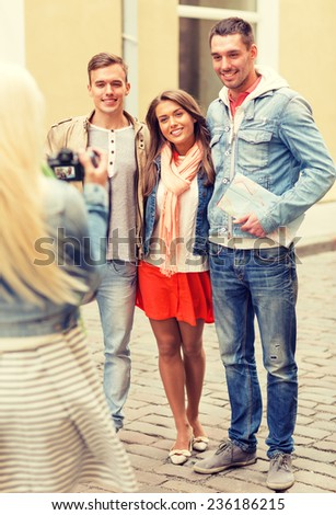 travel, vacation, technology and friendship concept - girl picturing group of friends with map in city - stock photo