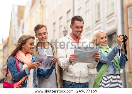 travel, vacation, technology and friendship concept - group of smiling friends with city guide, photocamera and map exploring city - stock photo