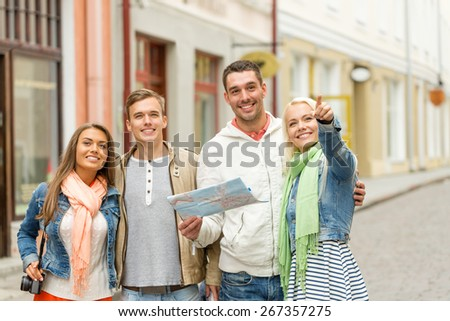 travel, vacation, technology and friendship concept - group of smiling friends with map and photocamera exploring city - stock photo