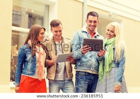 travel, vacation, technology and friendship concept - group of smiling friends with tablet pc computers in the city - stock photo