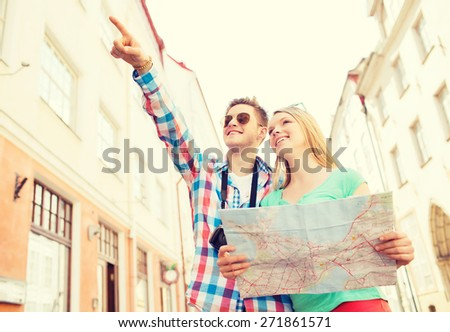 travel, vacation, technology and friendship concept - smiling couple with map and photo camera exploring city - stock photo