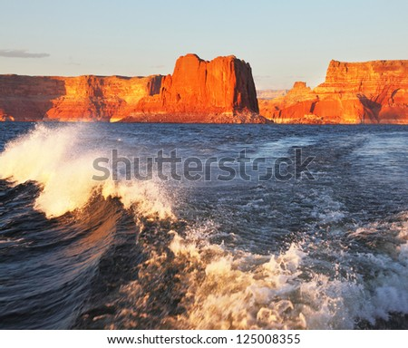 Travel voyage by boat on Lake Powell.  Scenic wave at the stern of the ship. Arizona, USA. Sunset - stock photo