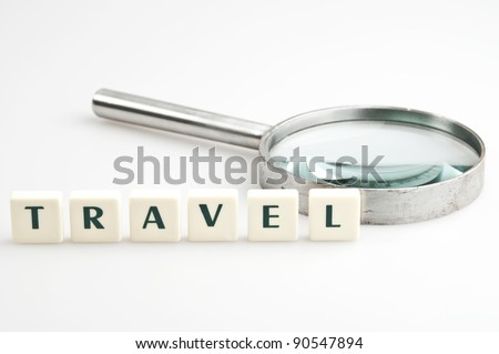 Travel word and magnifying glass - stock photo