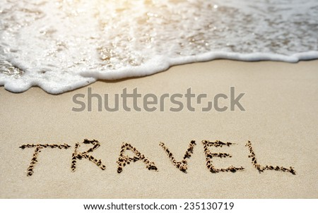 travel written on sandy beach near sea - stock photo