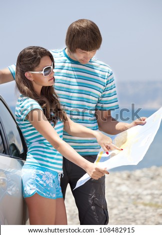Travel - young couple with car look at road map on a beach