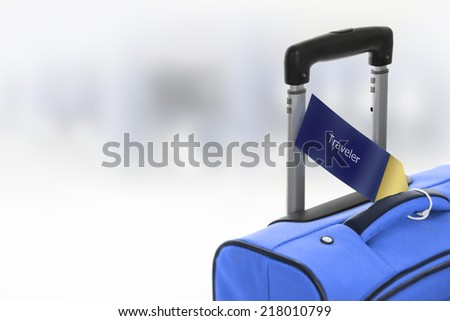 Traveler. Blue suitcase with label at airport. - stock photo