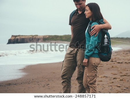 Traveler couple in love with backpacks walking on beach near the sea in summer. Man embracing a woman - stock photo