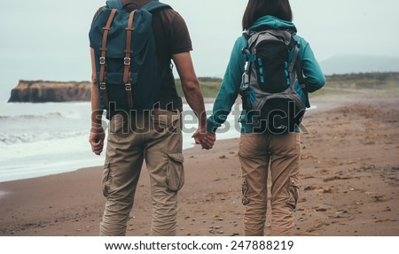 Traveler couple in love with backpacks walking on sea beach in summer and holding each other hand - stock photo