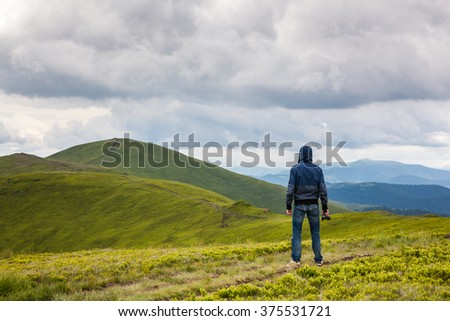 Traveler enjoying a beautiful view while hiking in mountains - stock photo