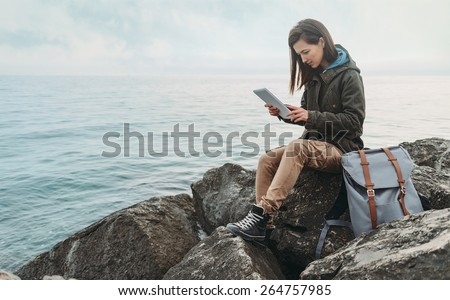 Traveler girl sitting on coast near the sea and working on digital tablet