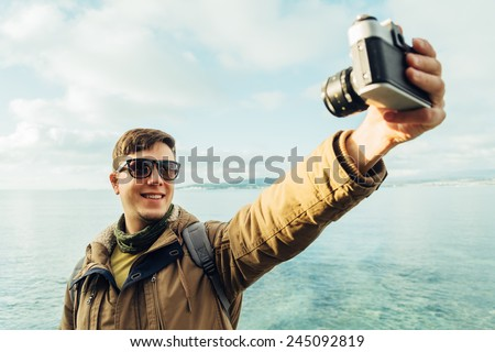 Traveler happy young man takes photographs self portrait with old photo camera on coastline on background of sea - stock photo