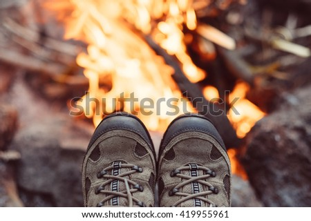 Traveler hiking boots in mountains near bonfire in travel. Trekking boots against fire, travel healthy active lifestyle freedom background. Feet selfie. Woman trekking boots relaxing outdoor. - stock photo