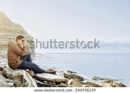 Traveler hipster young man sitting on coastline near the sea and taking photographs with vintage photo camera - stock photo