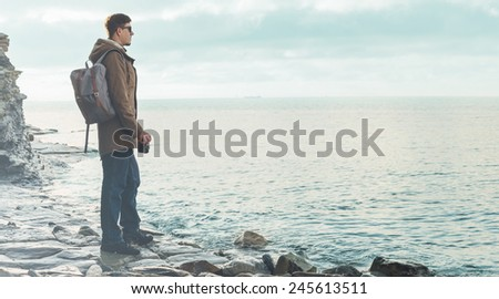 Traveler hipster young man standing on coastline near the sea with old vintage photo camera. Concept of travel and hiking - stock photo