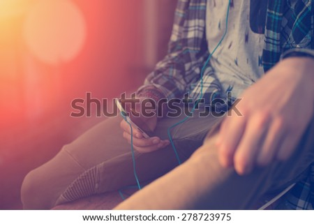 Traveler holding mobile phone with earphones, sitting on the top of the roof (intentional sun glare and vintage color) - stock photo