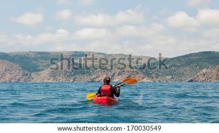 traveler kayaking in the thai ocean from backward view - stock photo