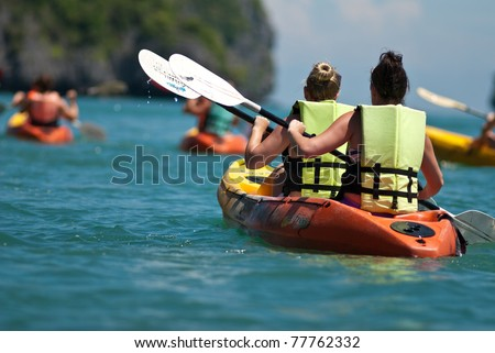 traveler kayaking in the thai ocean from backward view - stock photo