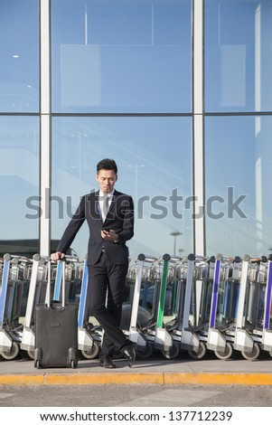 Traveler looking at cellphone next to row of luggage carts - stock photo