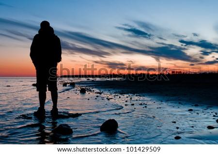 Traveler looking on sunset, standing in water near beach - stock photo