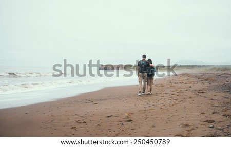 Traveler loving couple with backpacks walking on beach near the sea in summer. Man embracing a woman, rear view - stock photo