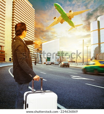 traveler man and luggage standing on traffic and looking to time watch against passenger car and airplane flying above - stock photo