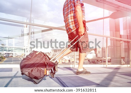 Traveler man at international airport moving to terminal gate for airplane travel - Wanderlust concept with solo person on the go - Rose quartz filter halo with focus on leg and blurred motion on bag - stock photo