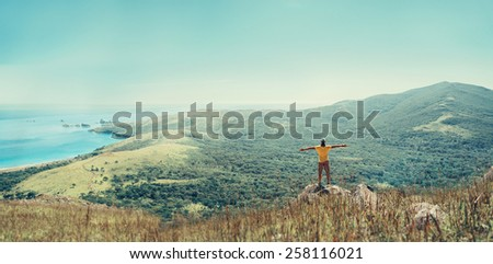 Traveler man standing with raised arms on peak of mountain near the sea and enjoying beautiful landscape in summer - stock photo