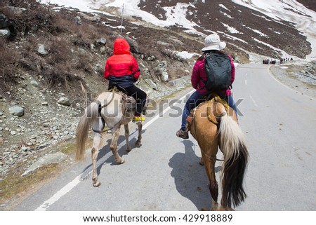 Traveler on horseback at road to snow mountain in Kashmir India - stock photo