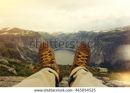 Traveler resting on a mountain plateau. POV view, legs close up on the background of mountain landscape