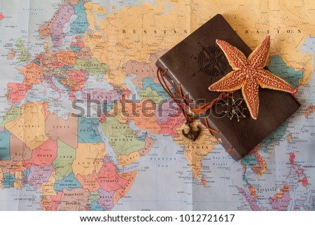 Travelers diary on world map starfish stock photo safe to use travelers diary on the world map a starfish and a leather covered notebook on gumiabroncs Gallery