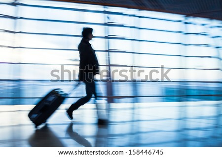 Traveler silhouettes at airport,motion blur,Beijing - stock photo