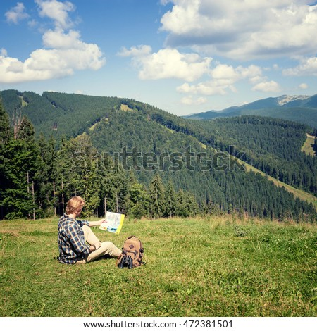 Traveler sitting on the alpine meadow and looking at the map