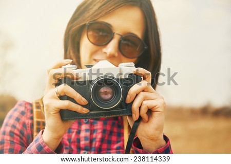 Traveler smiling young woman takes photographs with vintage old photo camera in spring outdoor. Focus on photo camera - stock photo
