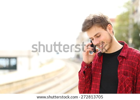 Traveler teen guy calling on the mobile phone in a train station while he is waiting  - stock photo