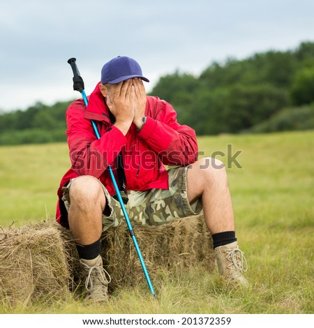 Traveler tired sitting relaxing after a trail holding trekking pole - stock photo